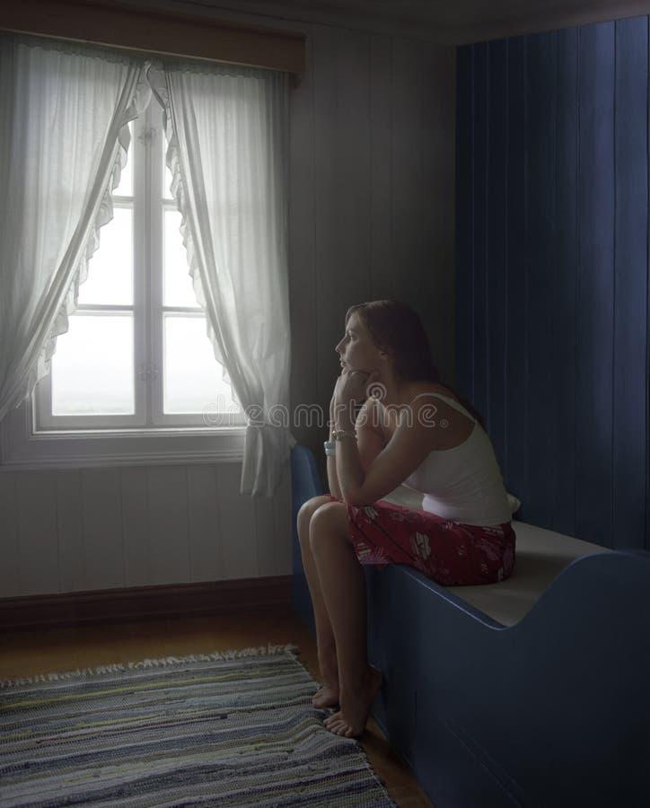 Donna triste che si siede da solo nella sala fotografia stock libera da diritti