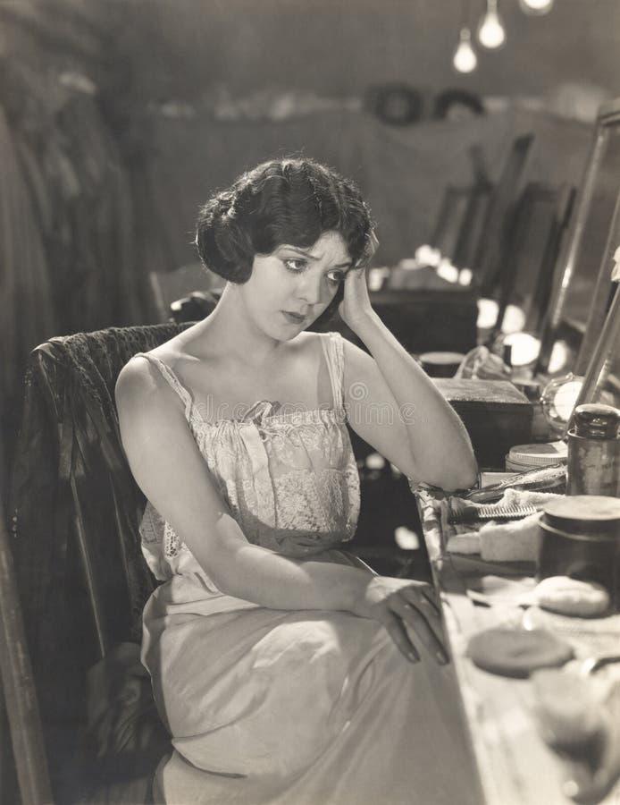 Donna triste che si siede nello spogliatoio fotografia stock