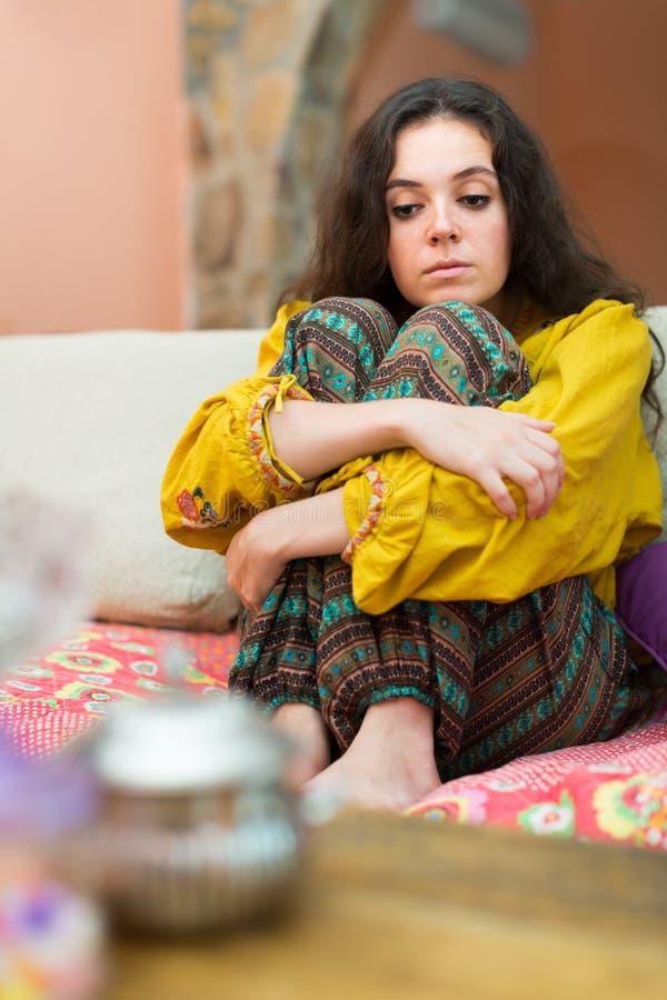 Donna triste che si siede sullo strato immagini stock libere da diritti