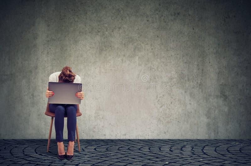 Donna triste con il computer portatile sulla sedia immagini stock libere da diritti