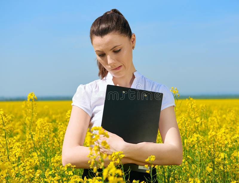 Donna triste di affari nel giacimento di fiore all'aperto con la lavagna per appunti Ragazza nel giacimento giallo del seme di ra fotografia stock libera da diritti