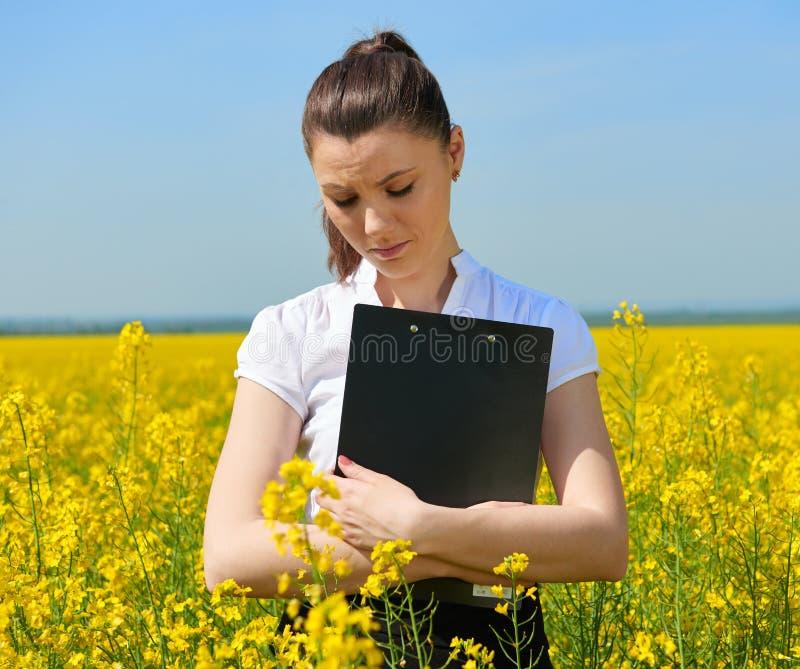 Donna triste di affari nel giacimento di fiore all'aperto con la lavagna per appunti Ragazza nel giacimento giallo del seme di ra immagini stock libere da diritti