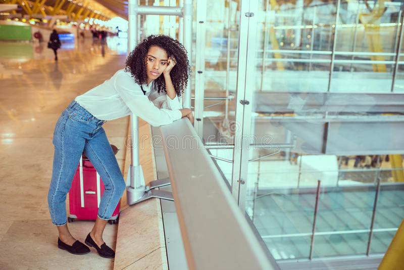 Donna triste ed infelice all'aeroporto con il volo annullato immagine stock