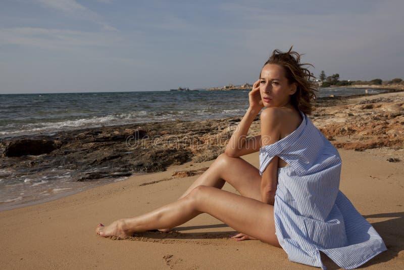 Donna triste sulla spiaggia fotografia stock