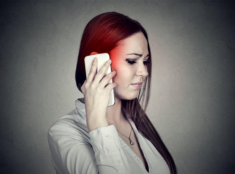 Donna triste turbata che parla sul telefono cellulare Concetto mobile cellulare di radiazione immagini stock