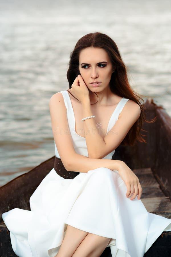 Donna triste in vestito bianco che si siede in una vecchia barca fotografia stock