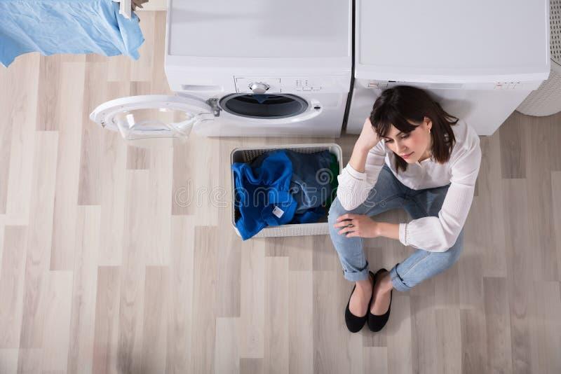 Donna turbata che si siede alla stanza di lavanderia fotografie stock libere da diritti