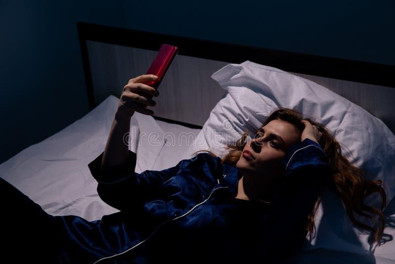 Donna turbata che si trova a letto in insonne immagini stock libere da diritti