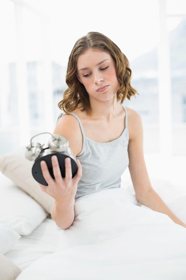 Donna turbata che tiene una sveglia che lo esamina che si siede sul suo letto fotografie stock