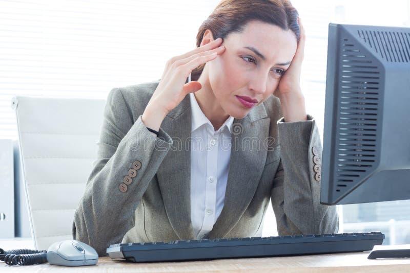Donna turbata di affari con la testa in mani davanti al computer all'ufficio immagini stock libere da diritti