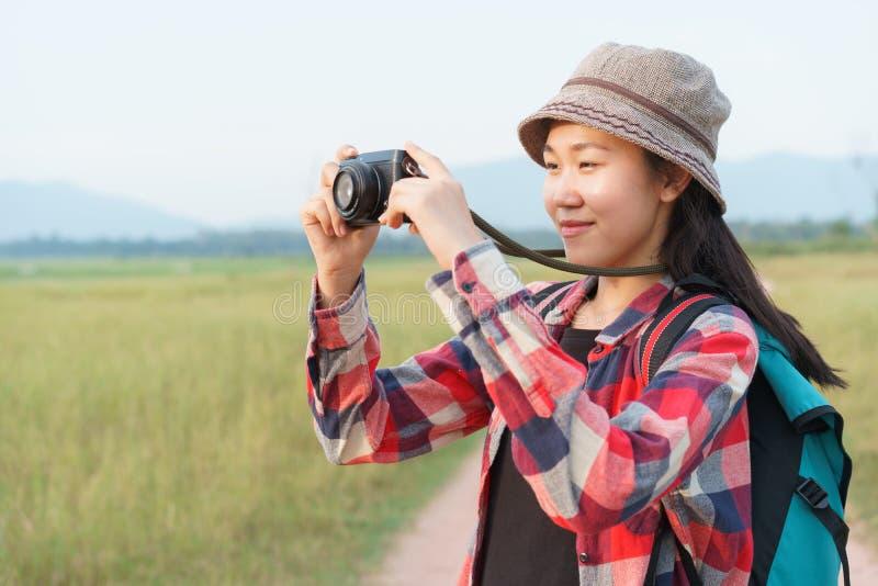 Donna turistica asiatica che prende foto dalla macchina fotografica digitale sul Mountain View della natura Una ragazza sta viagg immagine stock