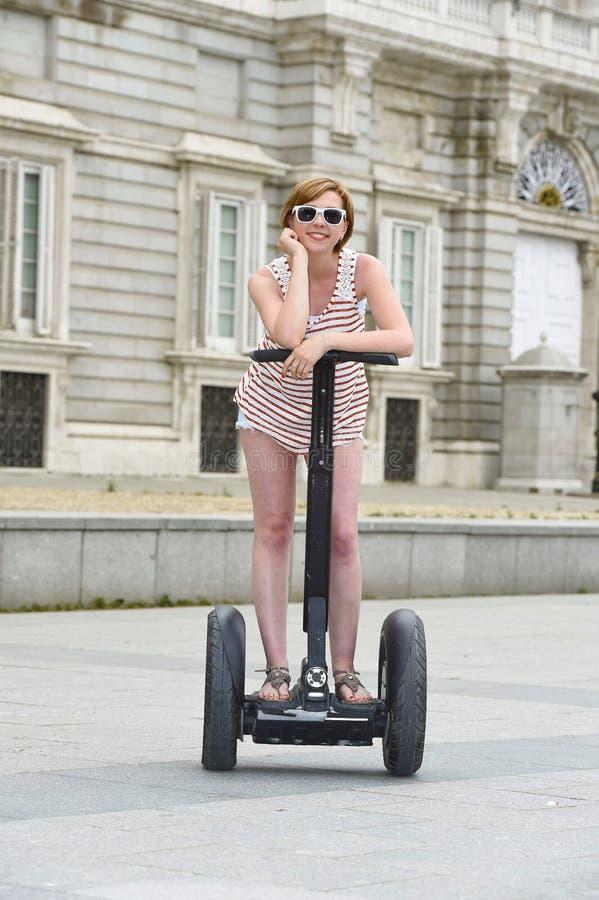 Donna turistica attraente giovane in breve il giro della città che guida segway elettrico felice in Spagna immagine stock libera da diritti