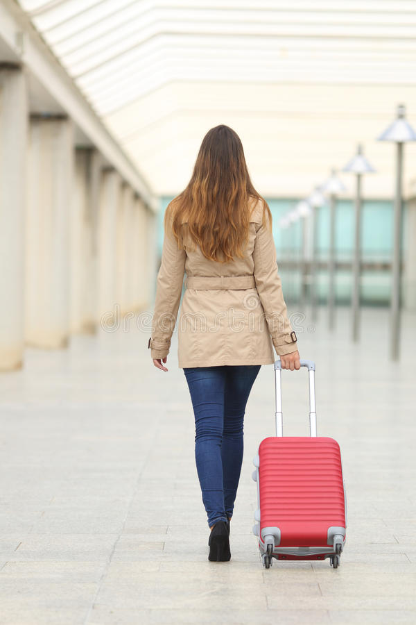 Donna turistica che cammina portando una cassa del vestito in un aeroporto fotografia stock