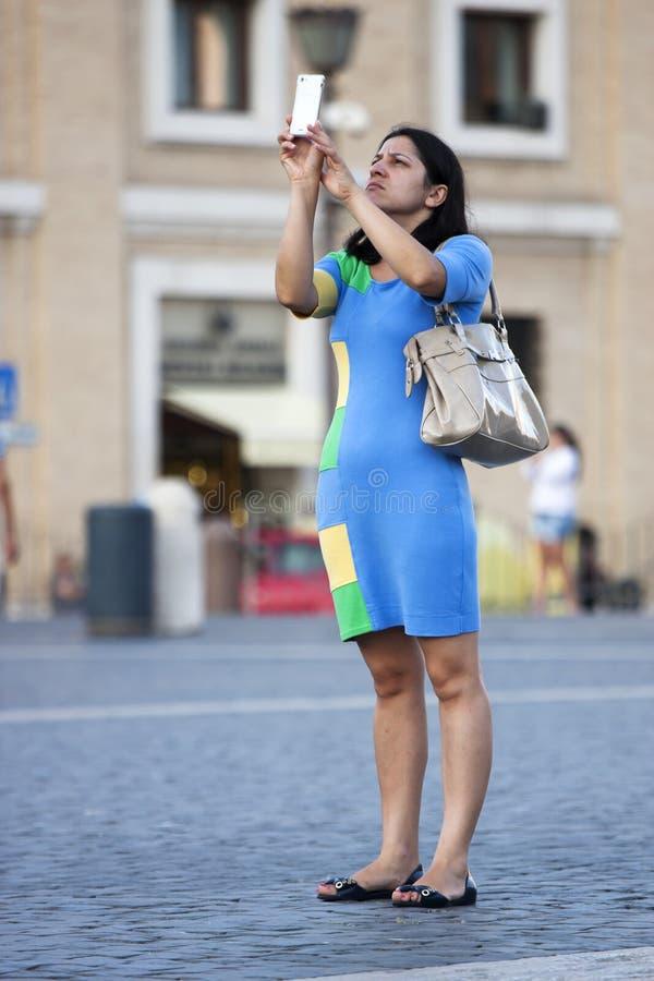 Donna turistica che prende una foto fotografia stock