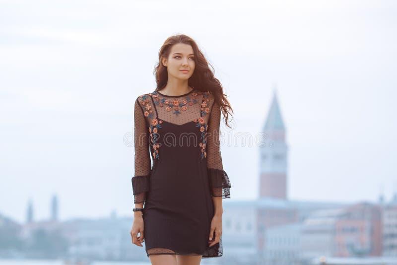 Donna turistica di viaggio sul pilastro contro la bella vista sul chanal veneziano a Venezia, Italia fotografia stock