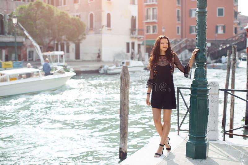 Donna turistica di viaggio sul pilastro contro la bella vista sul chanal veneziano a Venezia, Italia immagini stock libere da diritti
