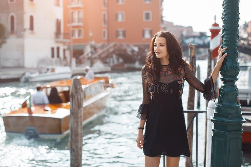 Donna turistica di viaggio sul pilastro contro la bella vista sul chanal veneziano a Venezia, Italia fotografia stock libera da diritti
