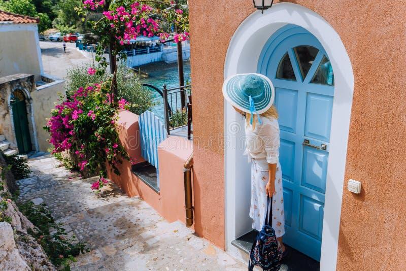 Donna turistica di viaggio sulla vacanza in Grecia Persona con il cappellino da sole blu davanti alla casa Mediterranea tradizion fotografie stock libere da diritti