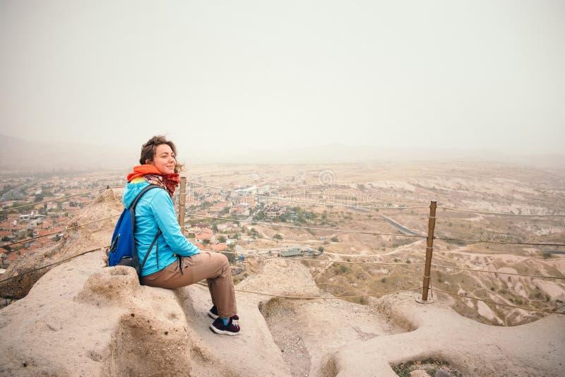 Donna turistica nella città di Uchisar che gode del paesaggio dal castello immagini stock libere da diritti