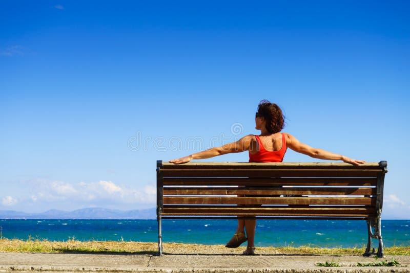 Donna turistica sul banco che gode della vista del mare fotografia stock libera da diritti