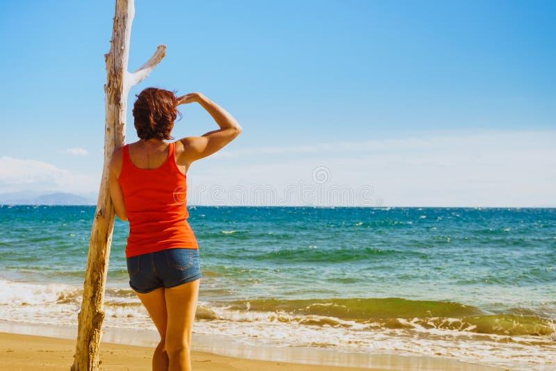 Donna turistica sulla spiaggia che gode della vacanza immagine stock libera da diritti