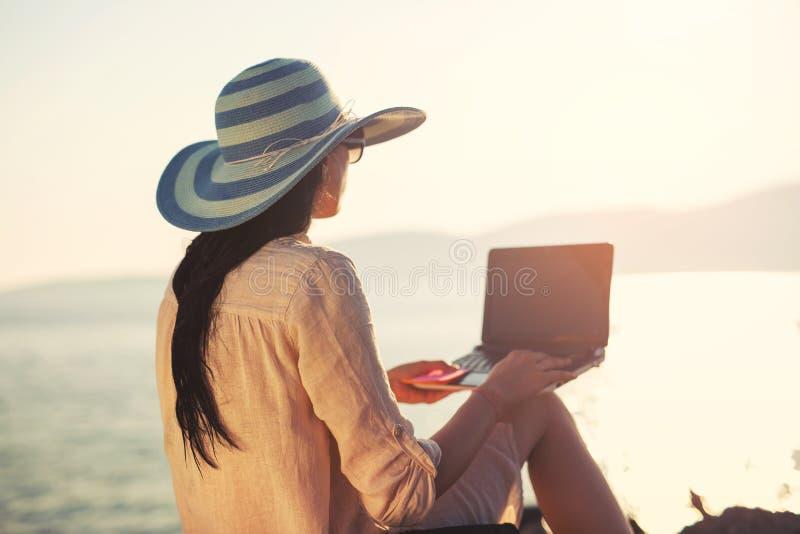 Donna turistica in vacanza che gode online con un computer portatile sulla spiaggia fotografia stock