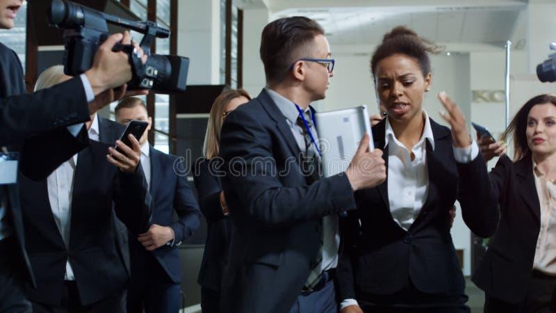Donna ufficiale con il responsabile fra il giornalista curioso fotografie stock libere da diritti
