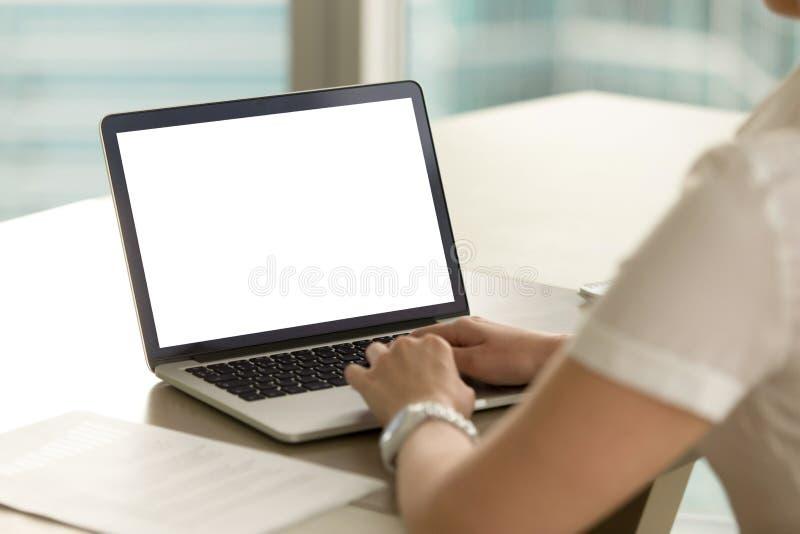 Donna in ufficio che lavora al computer portatile con lo schermo in bianco del modello immagine stock