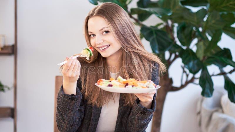 Donna in ufficio che mangia insalata al posto di lavoro Concetto di pranzo a lavoro ed a mangiare alimento sano Concetto sano di  fotografia stock