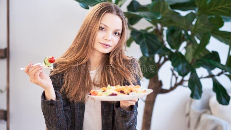 Donna in ufficio che mangia insalata al posto di lavoro Concetto di pranzo a lavoro ed a mangiare alimento sano Concetto sano di  immagini stock libere da diritti