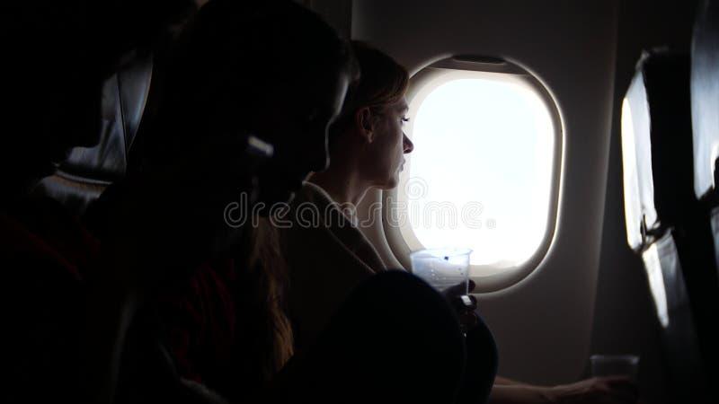 Donna in un aeroplano con i bambini su un fondo dell'oblò fotografie stock