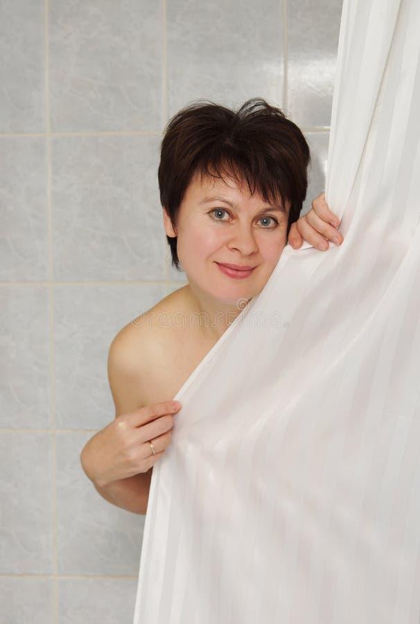 Donna in un bagno dietro la tenda fotografia stock