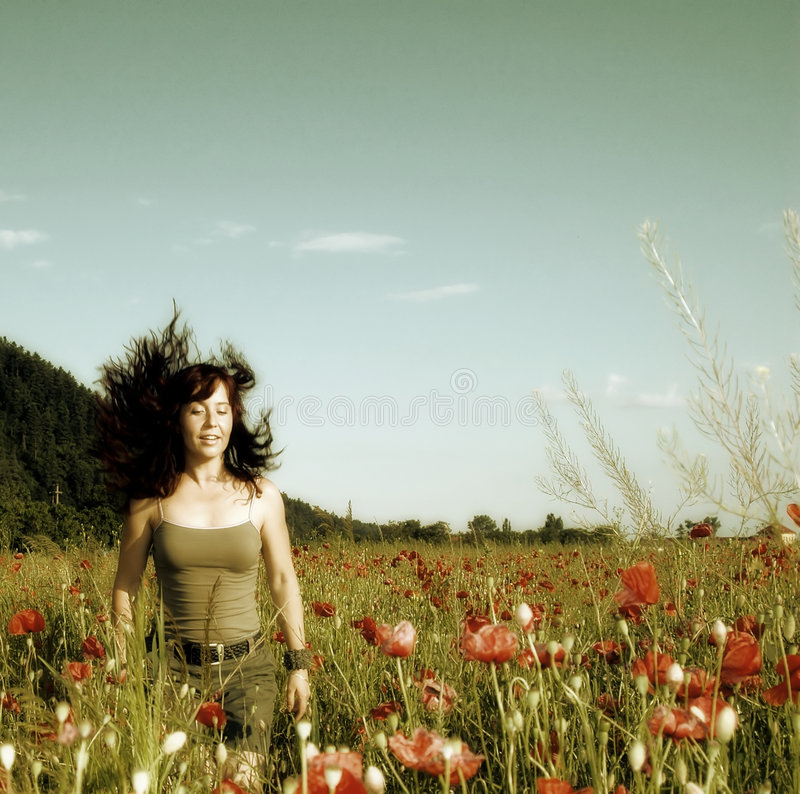 Donna in un campo del papavero fotografia stock libera da diritti
