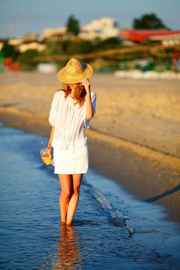 Donna in un cappello con succo d'arancia a disposizione sulla spiaggia immagine stock libera da diritti