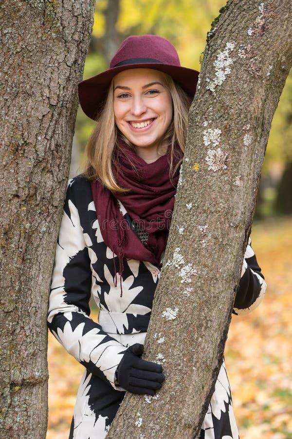 Donna in un cappello modellato floreale di rosso di vino e del cappotto nel parco, dal fiume Ragazza felice, ritratto variopinto  fotografia stock