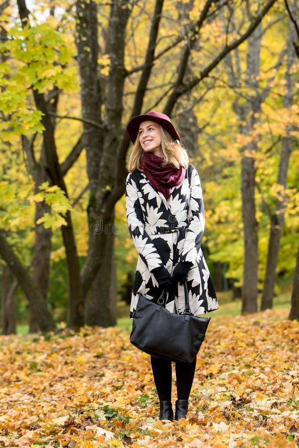 Donna in un cappello modellato floreale di rosso di vino e del cappotto nel parco, dal fiume Ragazza felice, ritratto variopinto  immagine stock libera da diritti