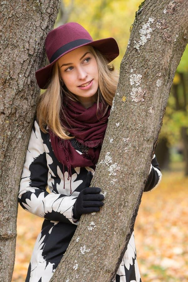 Donna in un cappello modellato floreale di rosso di vino e del cappotto nel parco, dal fiume Ragazza felice, ritratto variopinto  fotografie stock libere da diritti
