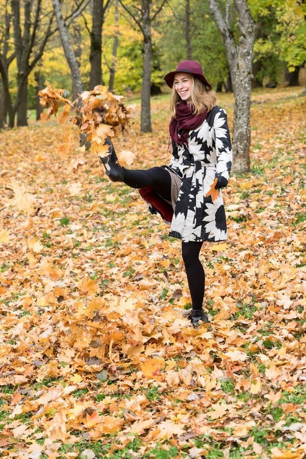 Donna in un cappello modellato floreale di rosso di vino e del cappotto nel parco, dal fiume Ragazza felice, ritratto variopinto  fotografia stock libera da diritti