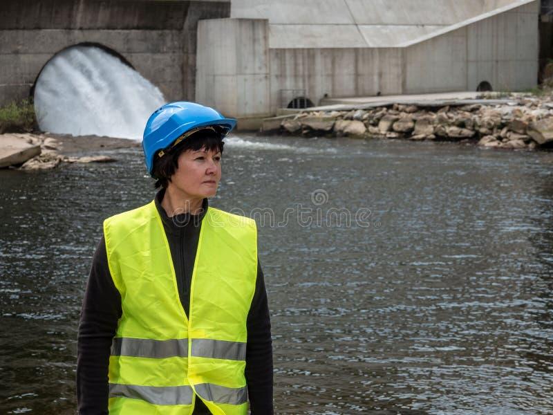 Donna in un casco contro il contesto delle turbine idroelettriche immagine stock