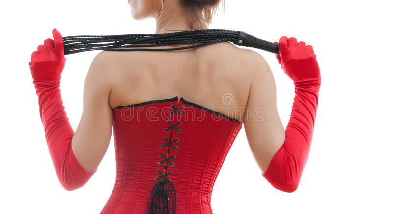 Donna in un corsetto ed in una frusta rossi immagine stock