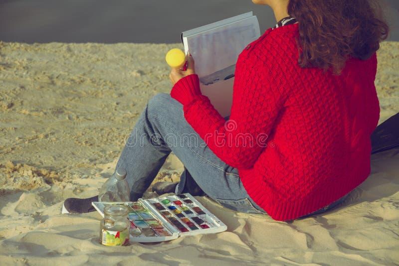 Donna in un maglione rosso che tiene una spazzola e che dipinge con acque di colore fotografia stock libera da diritti
