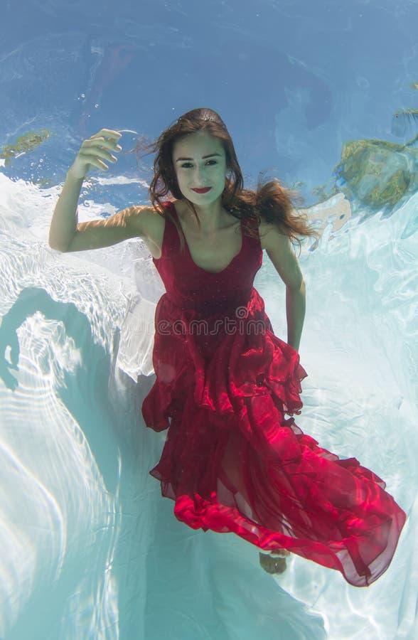 Donna in un vestito rosso subacqueo fotografia stock libera da diritti