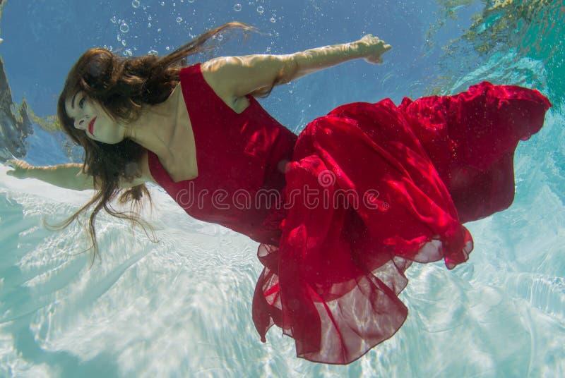 Donna in un vestito rosso subacqueo fotografie stock libere da diritti