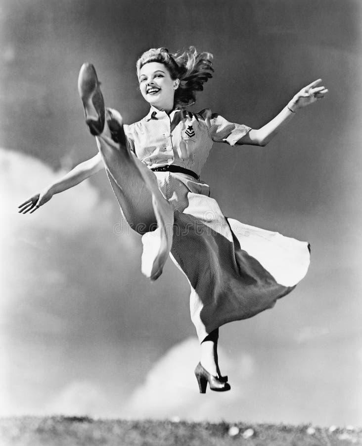 Donna in un vestito scorrente che salta attraverso l'aria (tutte le persone rappresentate non sono vivente più lungo e nessuna pr fotografia stock libera da diritti