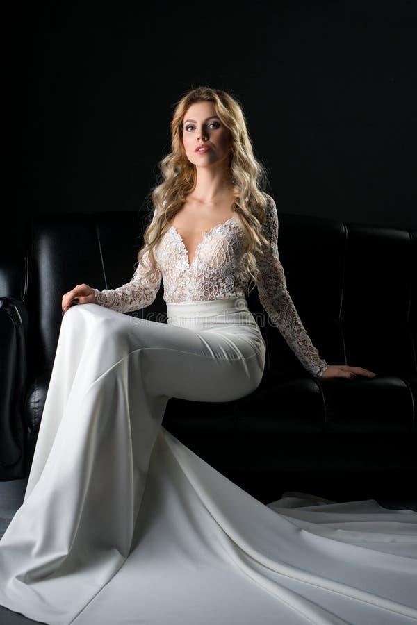 Donna in un vestito uguagliante dal pizzo che si siede sul sofà immagini stock libere da diritti