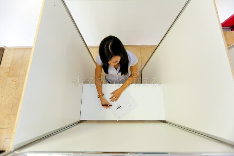 Donna in una cabina di voto immagini stock