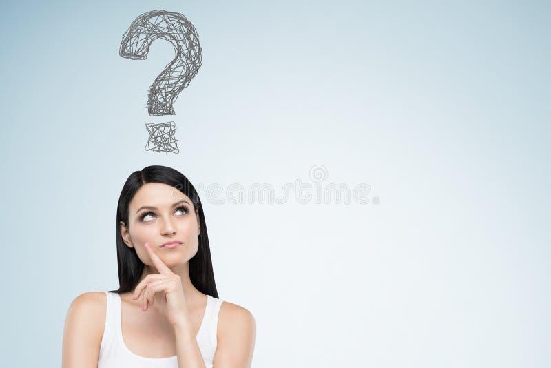 Donna in una canottiera sportiva ed in un punto interrogativo sulla parete blu fotografia stock