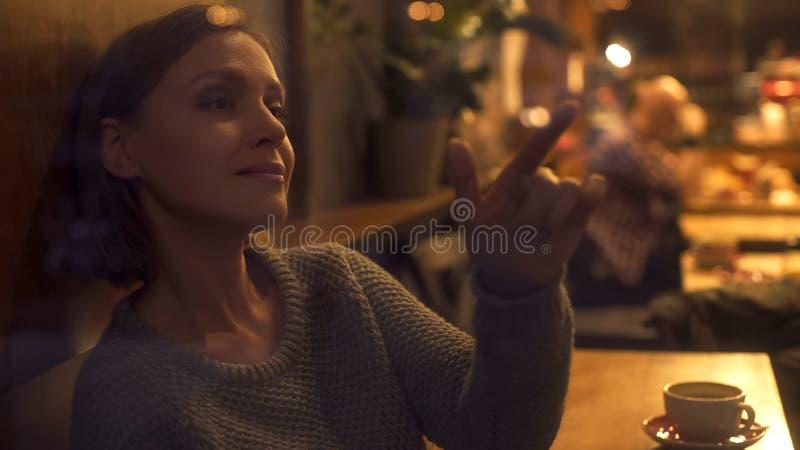 Donna vaga che tocca finestra, sedendosi in caffè accogliente, scrivente messaggio, umore immagini stock