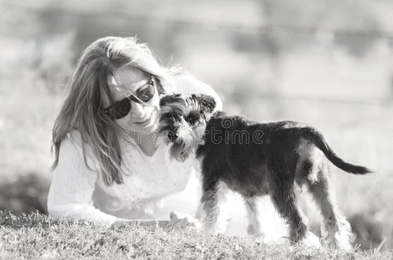 Donna vaga molle a basso contrasto di tenerezza di amore e cucciolo di cane dell'animale domestico immagine stock libera da diritti