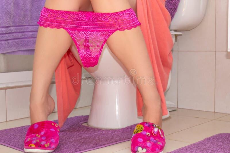 Donna in vestaglia e pantofole nella toilette Tonificato vicino sull'immagine di un giovane sexy con la seduta piegata mutandine  immagine stock